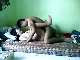 Nepali young horny couple in bed with the guy hiking the babes kameez to expose her big mouth watering tits and suck and fondle them one by one during sex foreplay.
